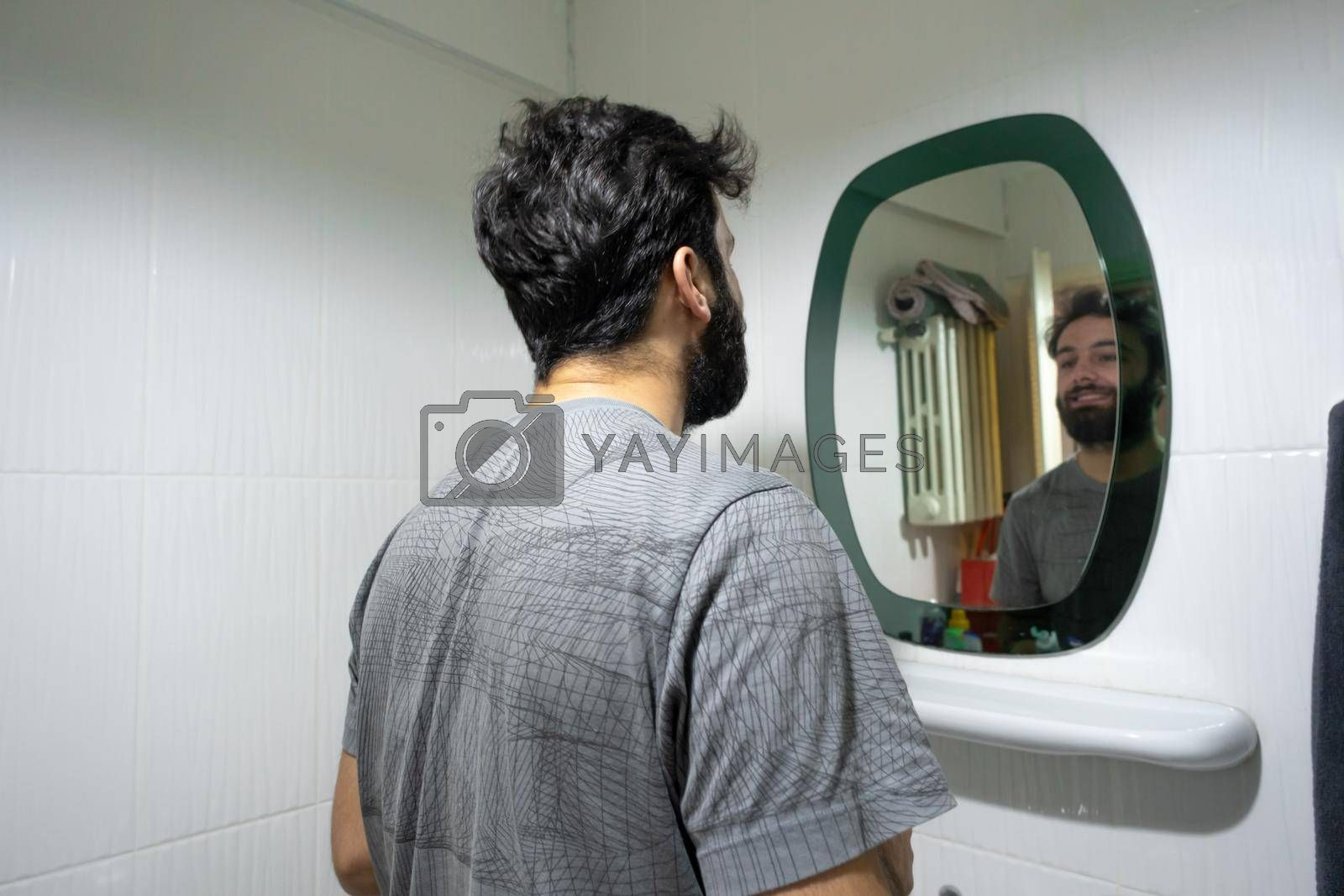 It depicts a man standing in front of a mirror in bathroom lifestyle concept
