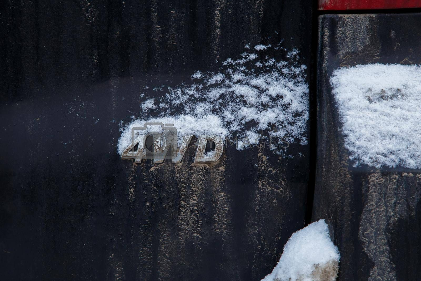 an abbreviation 4wd - four wheel drive - on dirty black car back, with snow