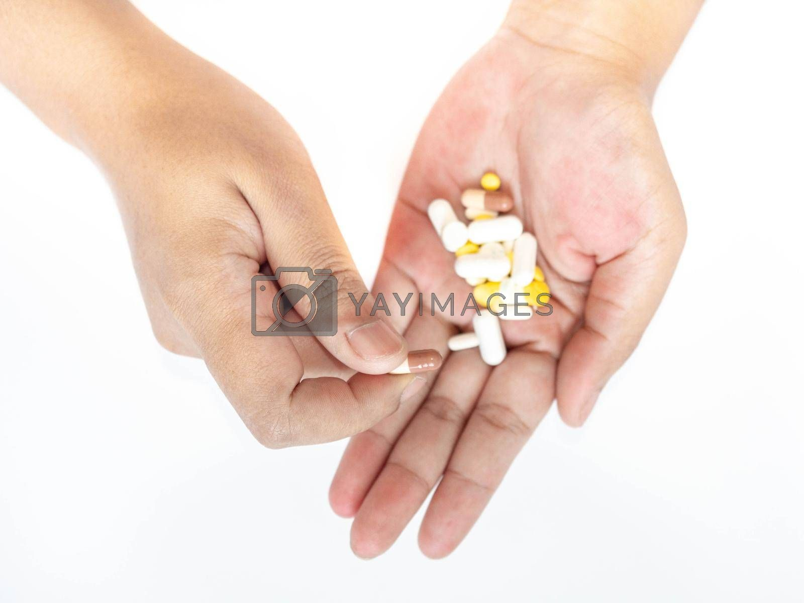 A woman picks up a pill from her hand White background.