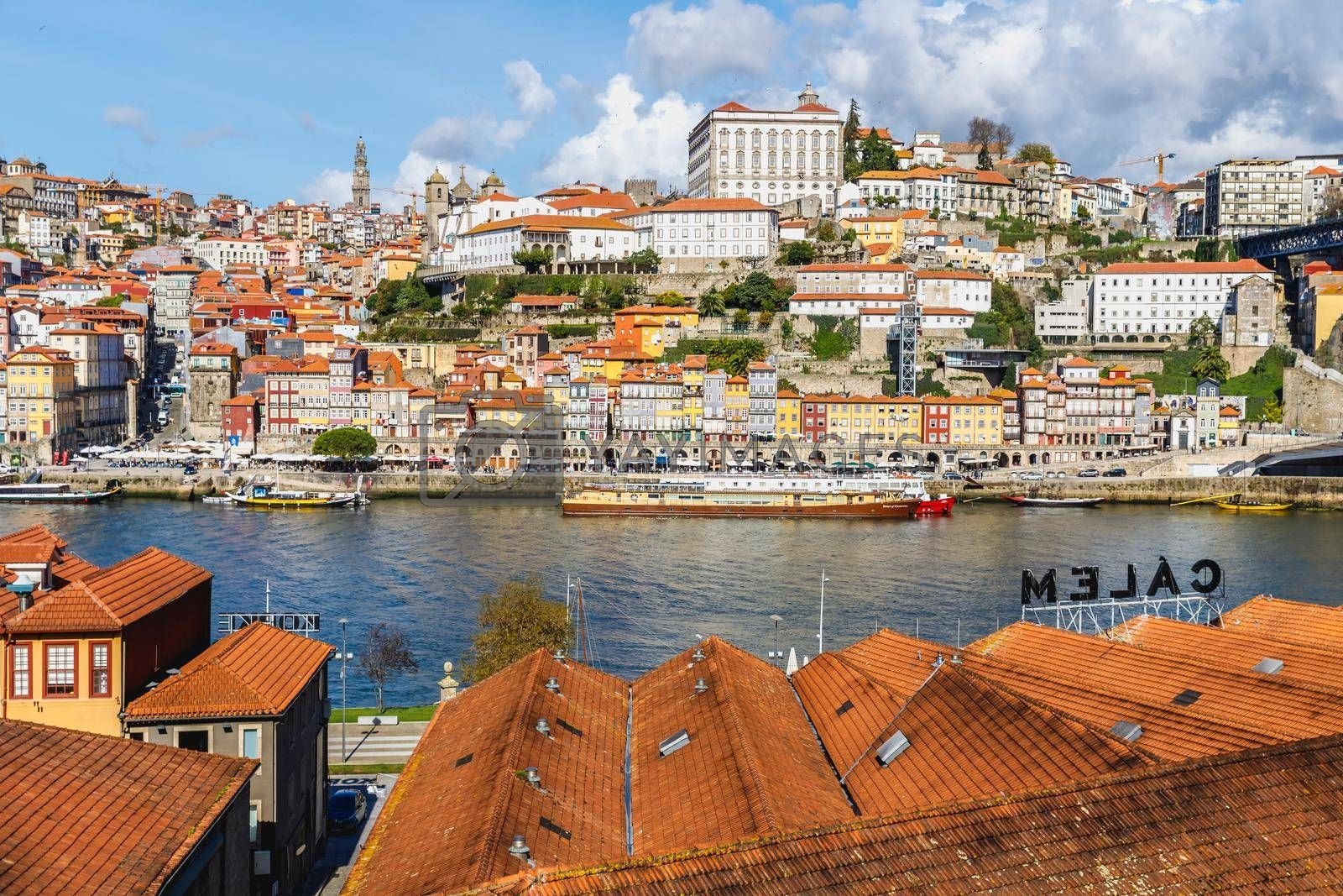 Porto, Portugal - October 23, 2020: View of the buildings with typical architecture and boats of tourist areas on the banks of the Douro river on an autumn day