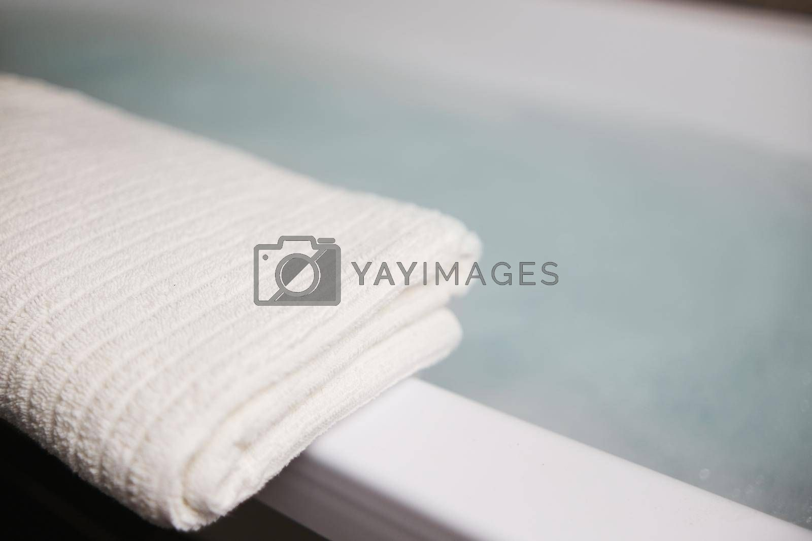 A white towel on the edge of the tub. Blurred background gray blue colors.