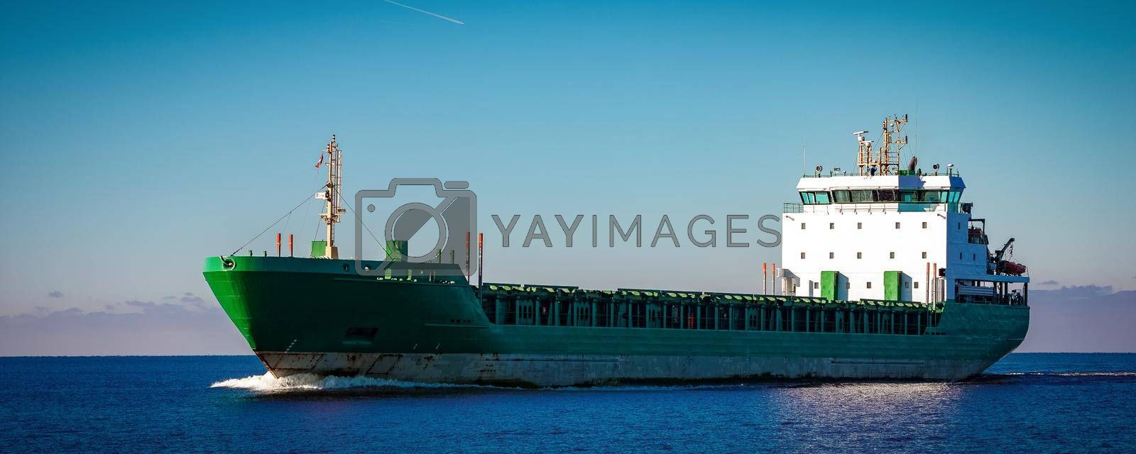 Green cargo ship moving in still water of Baltic sea