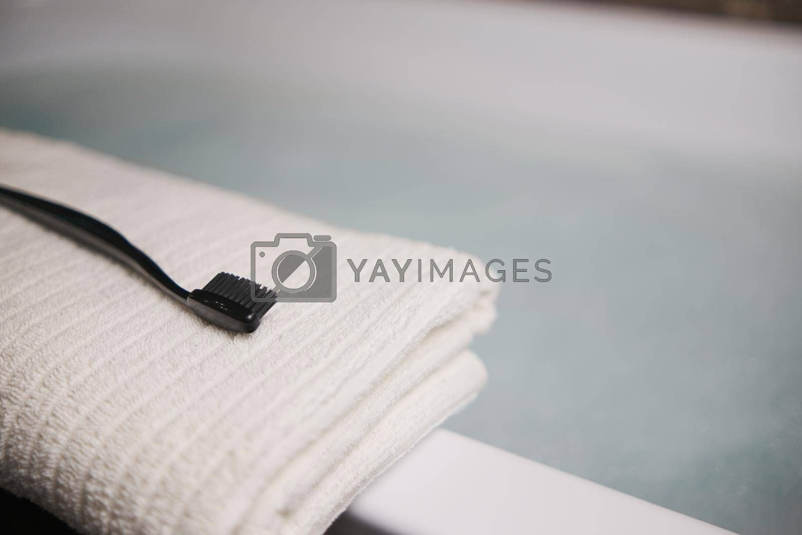A black toothbrush on a white towel in the bathroom. Blurred background Gray Blue colors.