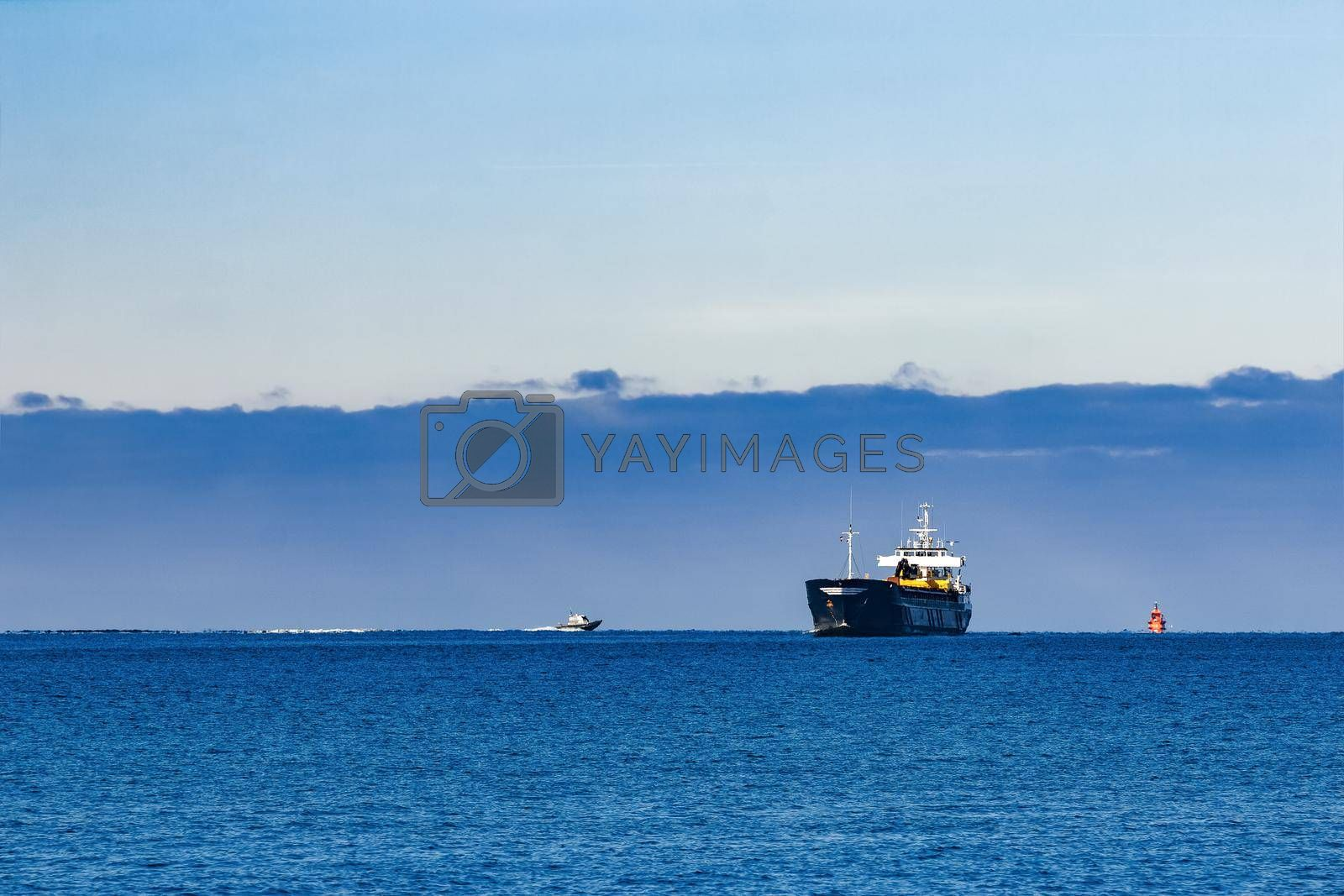 Black Sailing Bulk Carrier. Cargo Ship with Long Reach Excavator Moving in Still Water at Sunny Day by the Sea