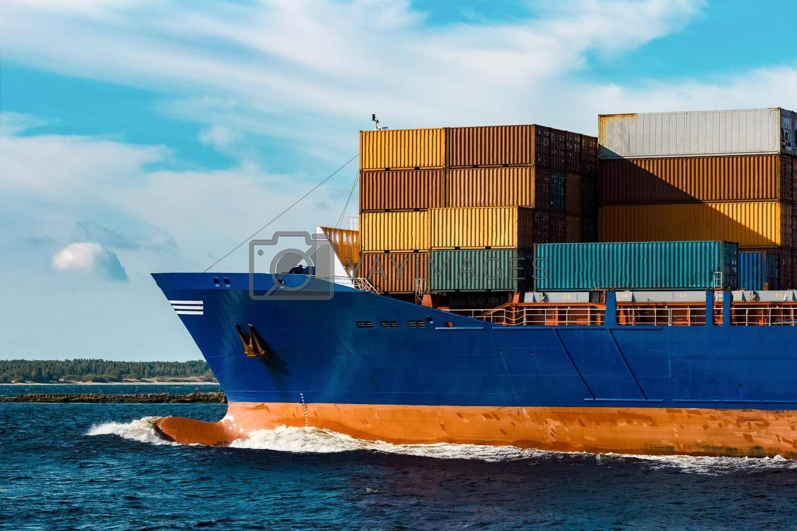 Blue container ship in travel. Logistics and freight industry