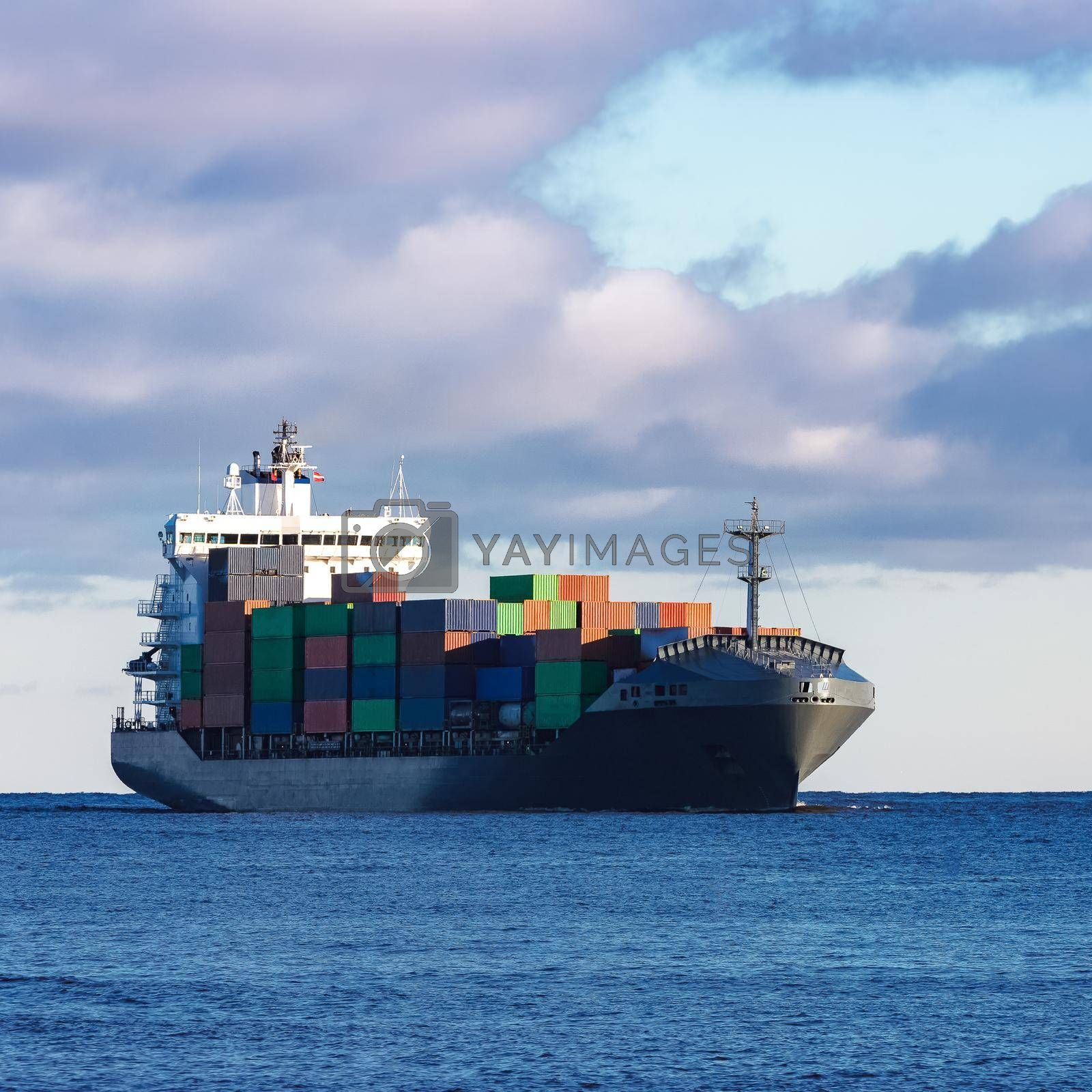 Modern grey container ship moving in still water