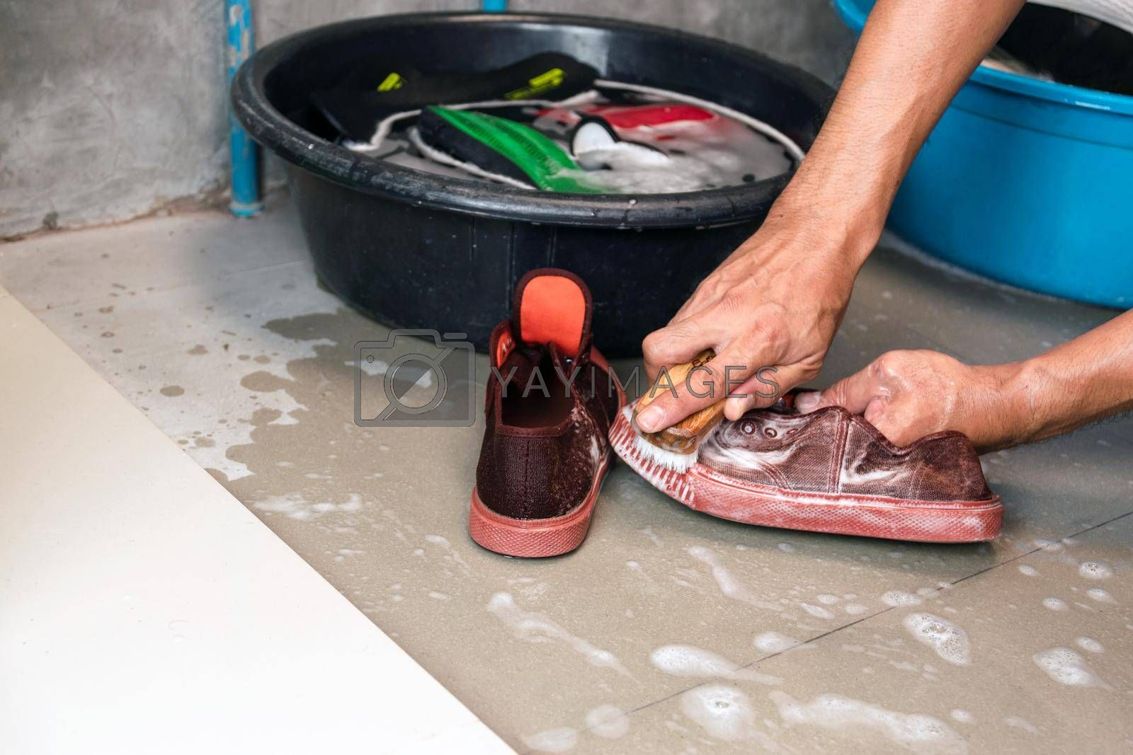Washing the sneakers with a washing brush and washing powder.