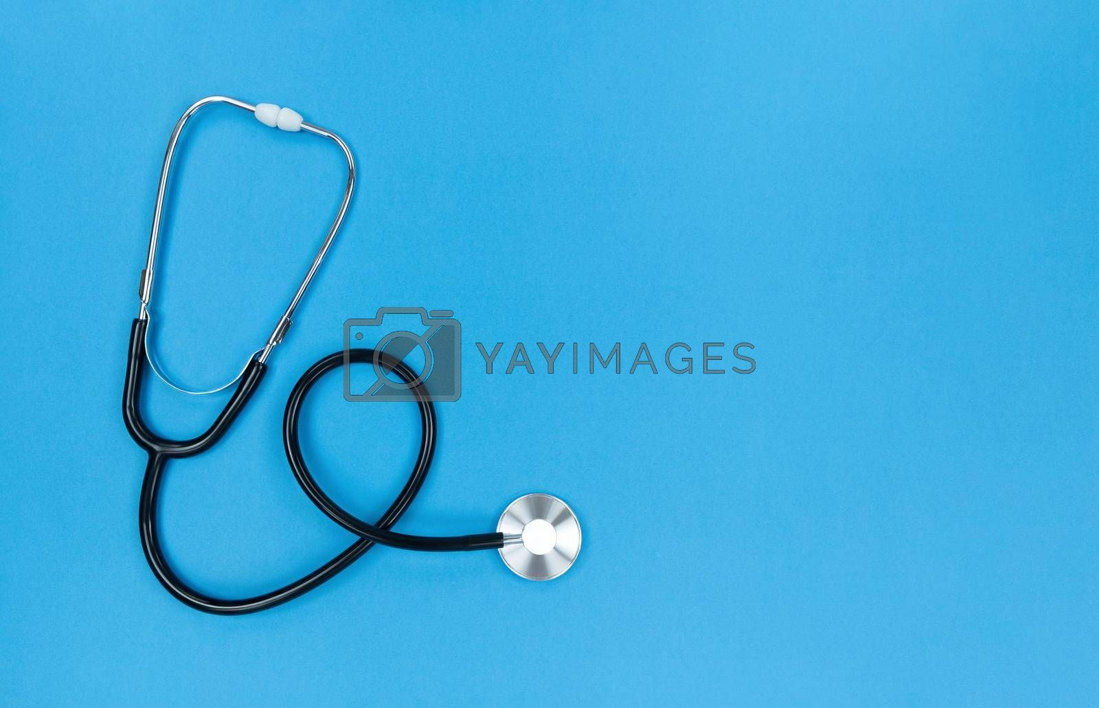 Black stethoscope on a blue background. Simple flat lay with copy space.