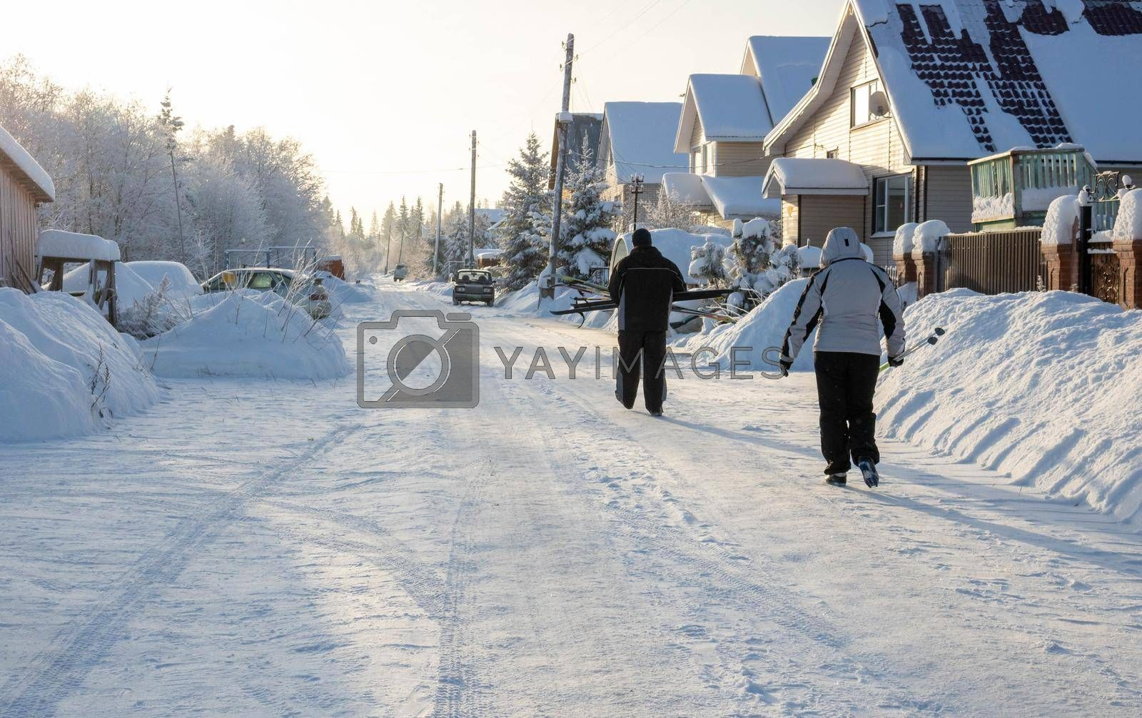 Frosty rural road landscape. Winter snow-covered rural road. People are coming from a ski trip, faces are not visible.