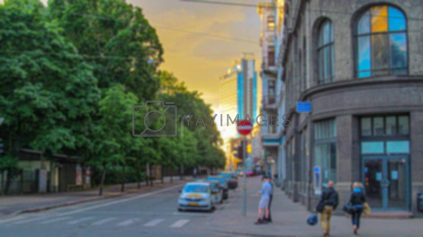 Blurred background of a city street. Urban landscape. Creative theme with blur and bokeh effect for backgrounds, posters and screensavers.