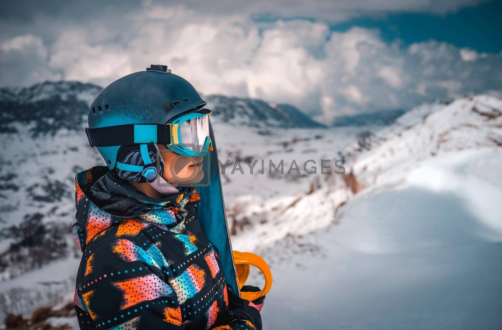 Profile Portrait of Snoeboarder Girl Looks into the Distance at a Beautiful Winter Mountain Landscape. Active Peoplel Enjoying Ski Resort.