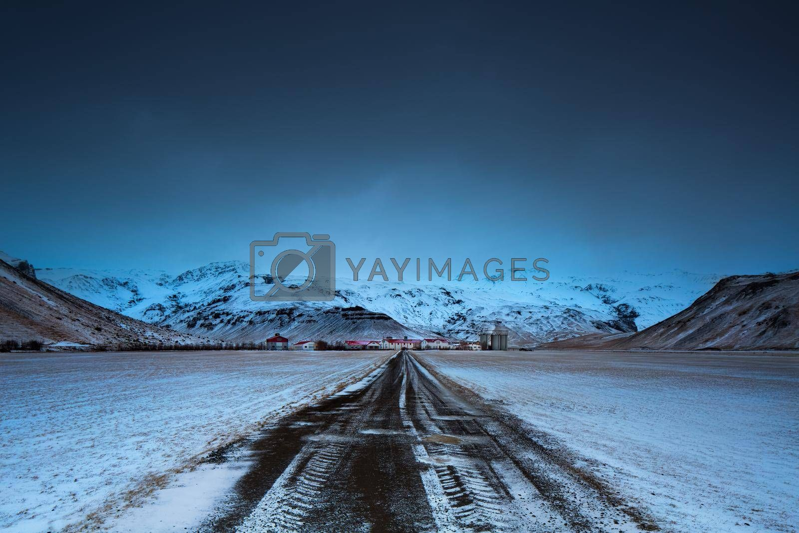 Beautiful Winter Landscape. Road Leads to a Small Village Located at the Foot of High Mountains Covered with Snow. Travel to Iceland.