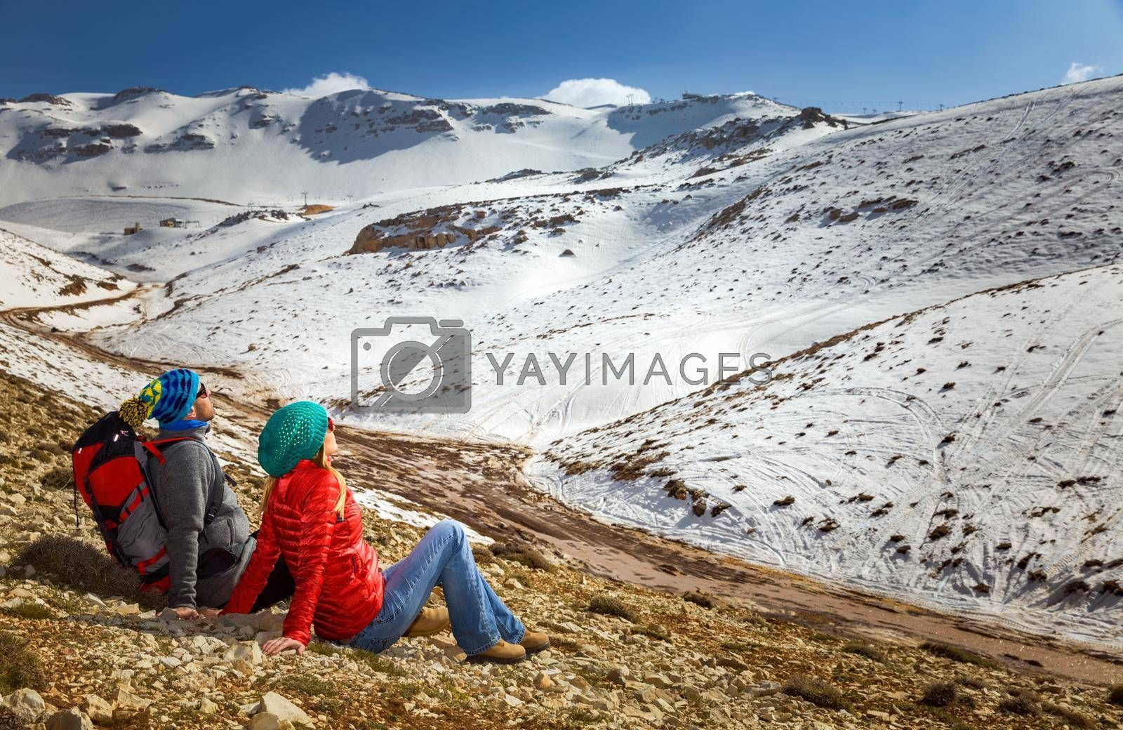 Happy Young Couple Sitting and Resting in the Mountains at Base Camp. Enjoying Adventure Hike in the beautiful Snowy Mountains. Active Sportive Lifestyle. Winter Holidays Concept.