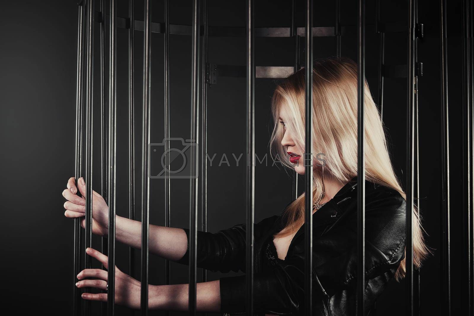 A beautiful, glamour young blond Girl in a black jacket is posing in an iron forged cage. The concept of domestic violence by Nickstock