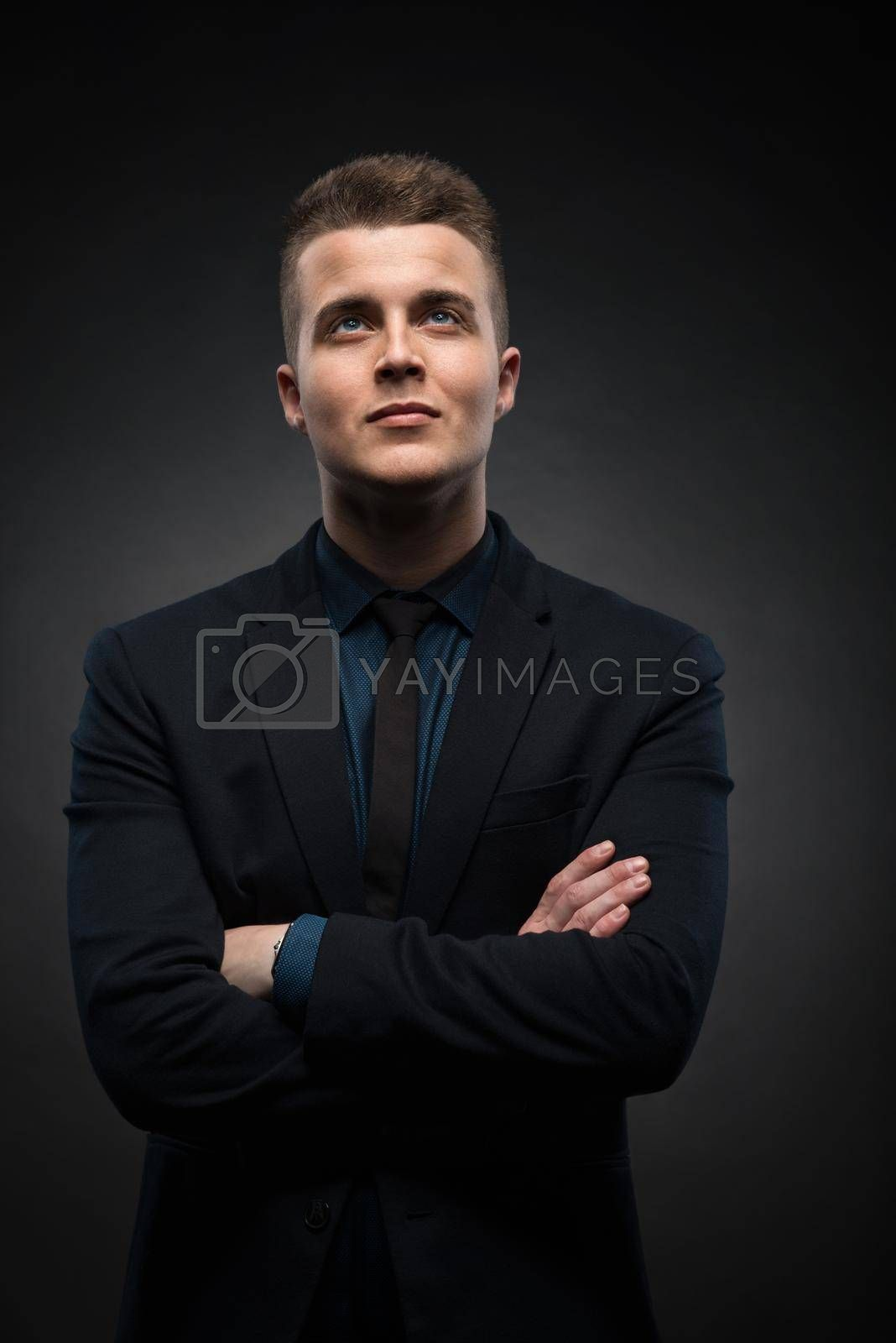 a portrait of a handsome young businessman is thinking and looking up against a black background by Nickstock