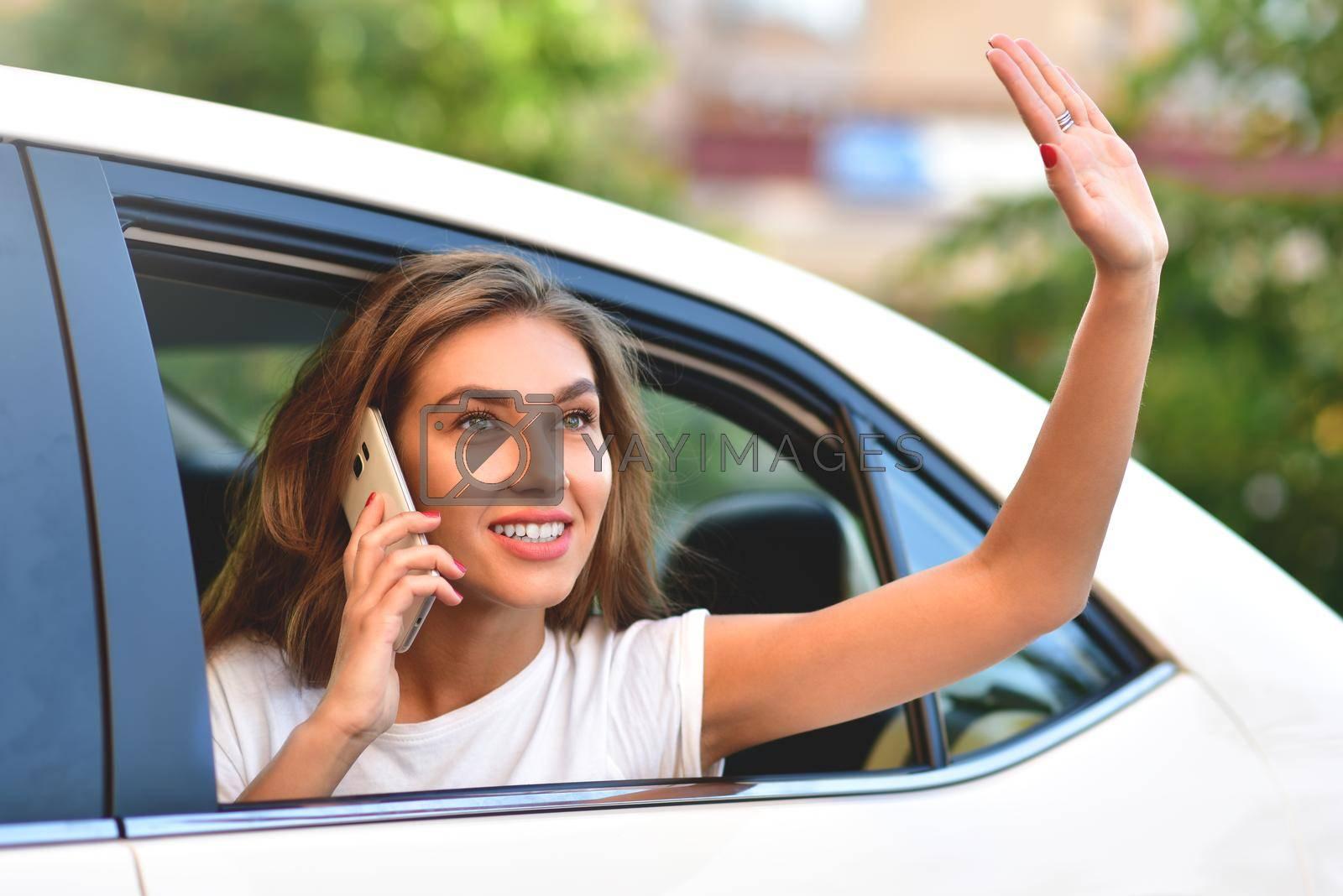 Woman peeking out of car window, woman peeking out of window and waving her hand by Nickstock