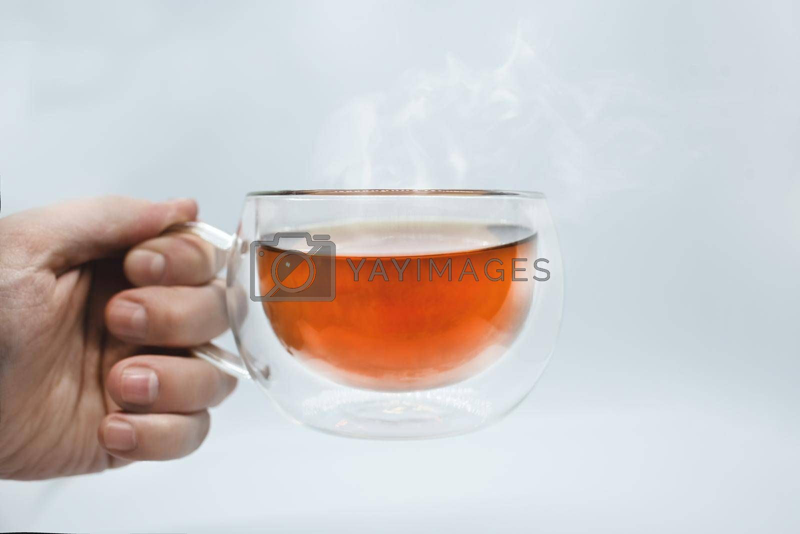 Man's hand holding a transparent cup with tea. Isolated on white background. Alpha by Nickstock
