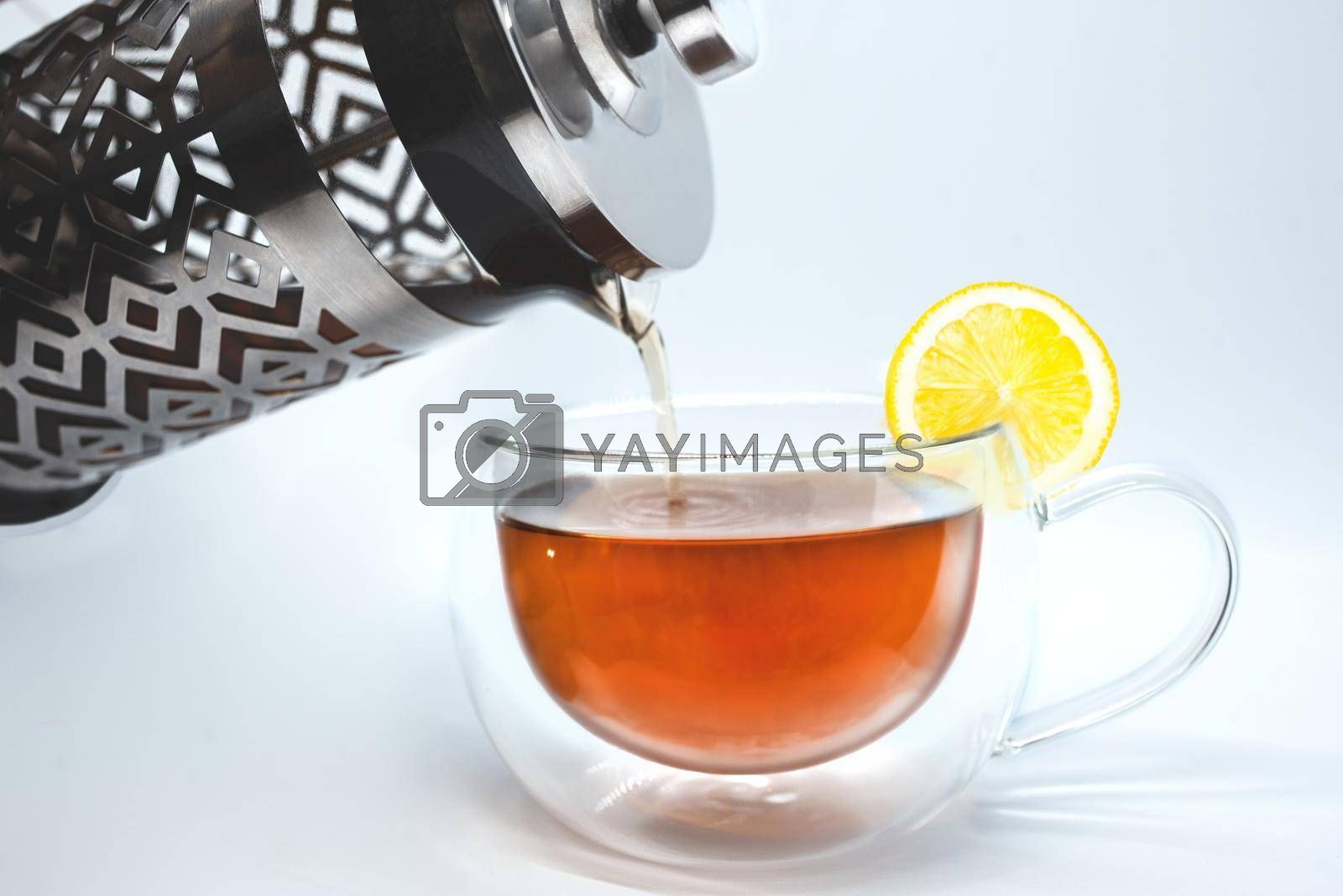 Glass teapot pouring black tea into cup isolated on white by Nickstock