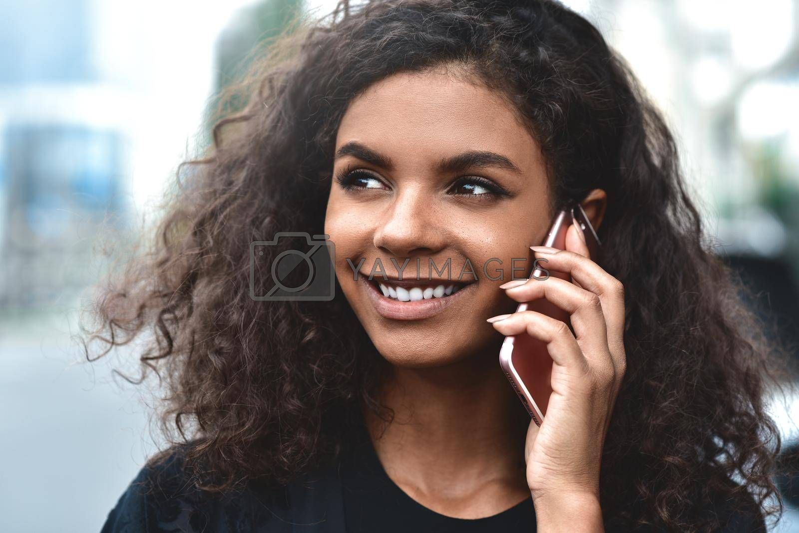 Positive emotions. Lifestyle concept. Close up of young mixed race woman use a phone. by Nickstock