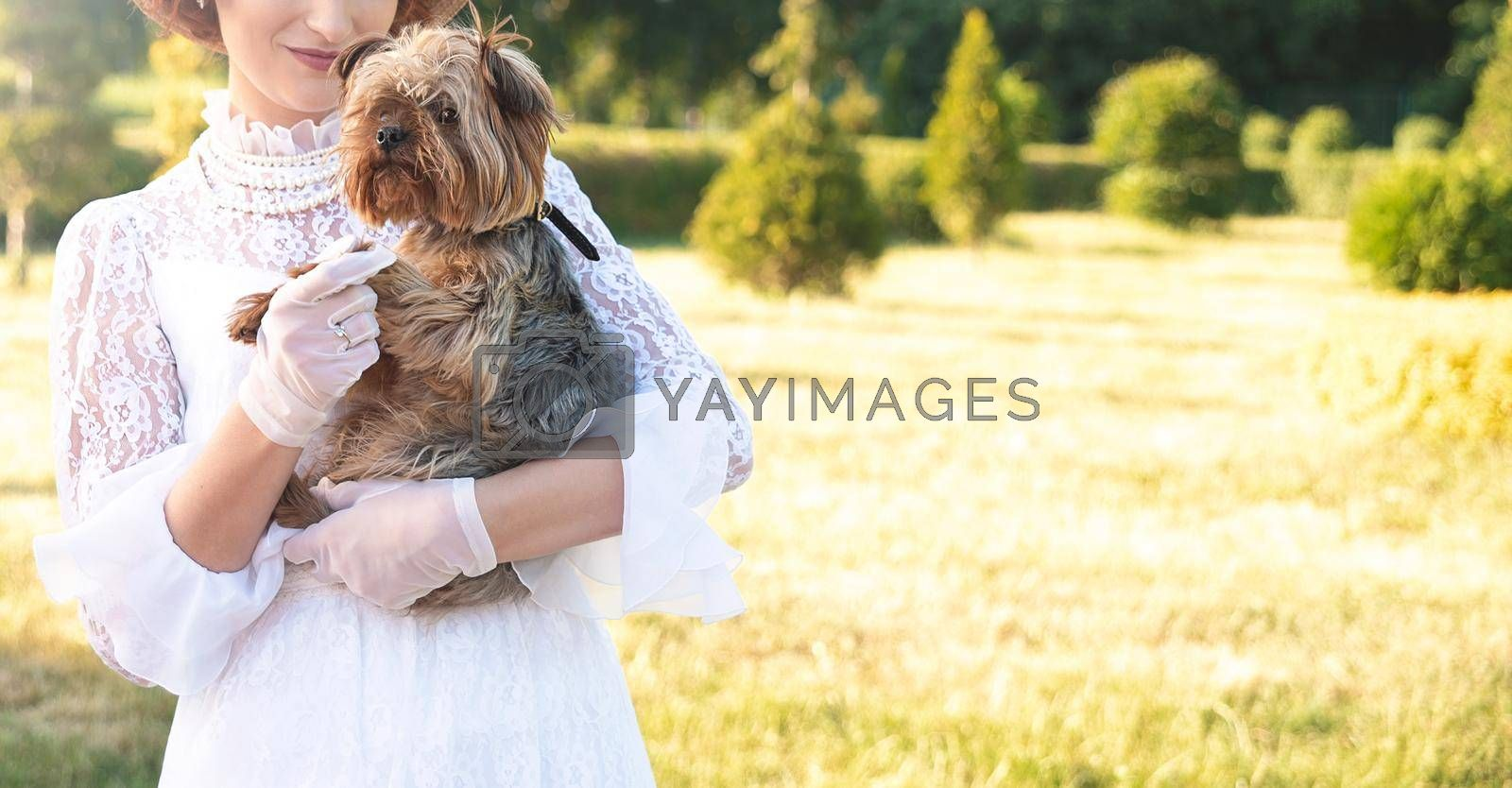 Retro portrait of a beautiful woman holding Yorkshire terrier by Nickstock