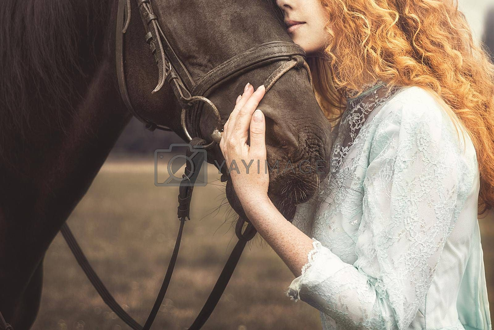 Artistic photo. young Woman with no face dressed in an elegant vintage dress, gently cuddling a horse, stroking his head. love for animals by Nickstock