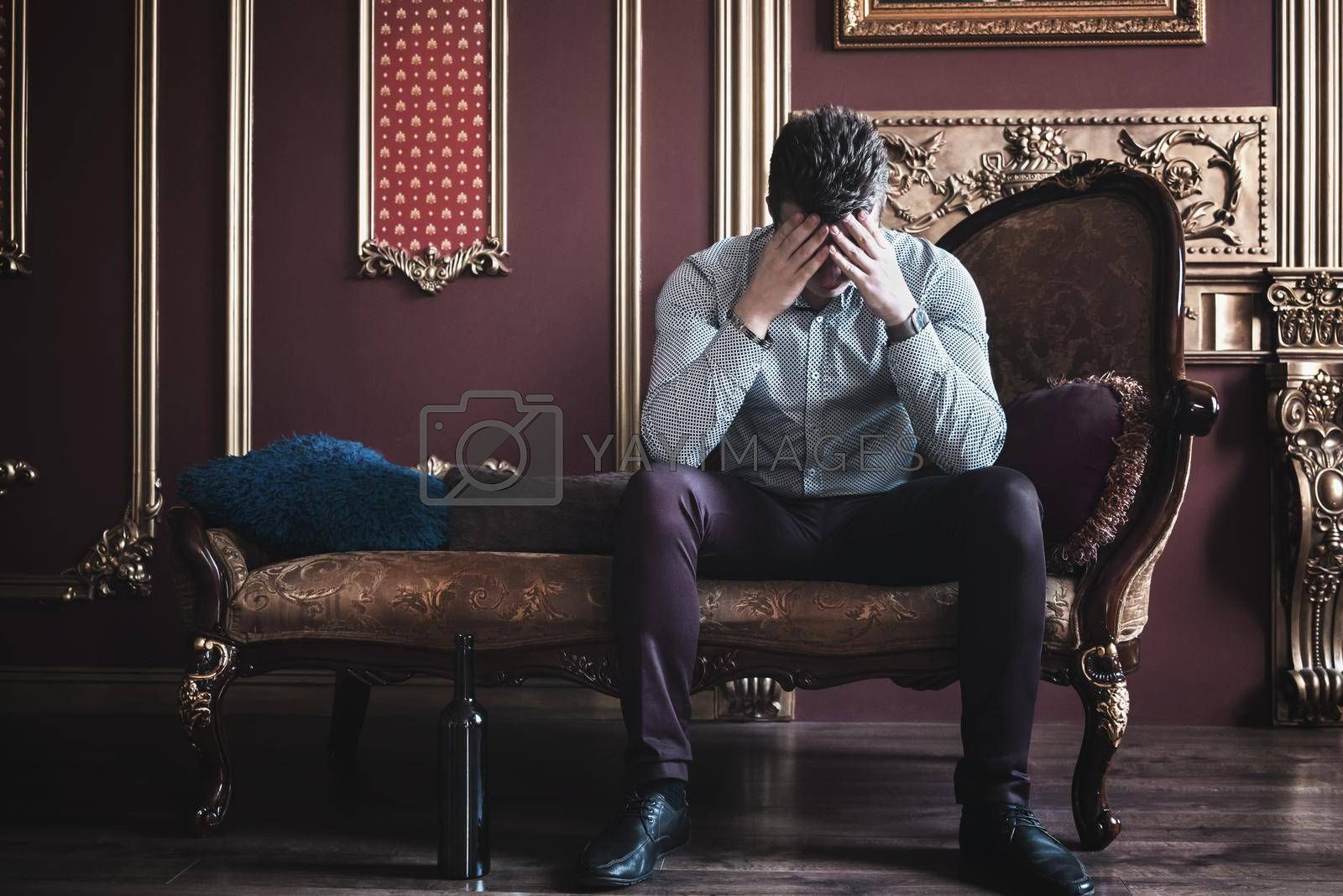 depressed Young businessman is sitting on sofa in the room, holding hands on his head. Concept of human emotions. Copy space by Nickstock
