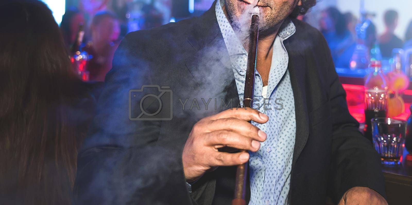 a man with no face smokes a hookah slowly exhaling smoke at the nightclub by Nickstock