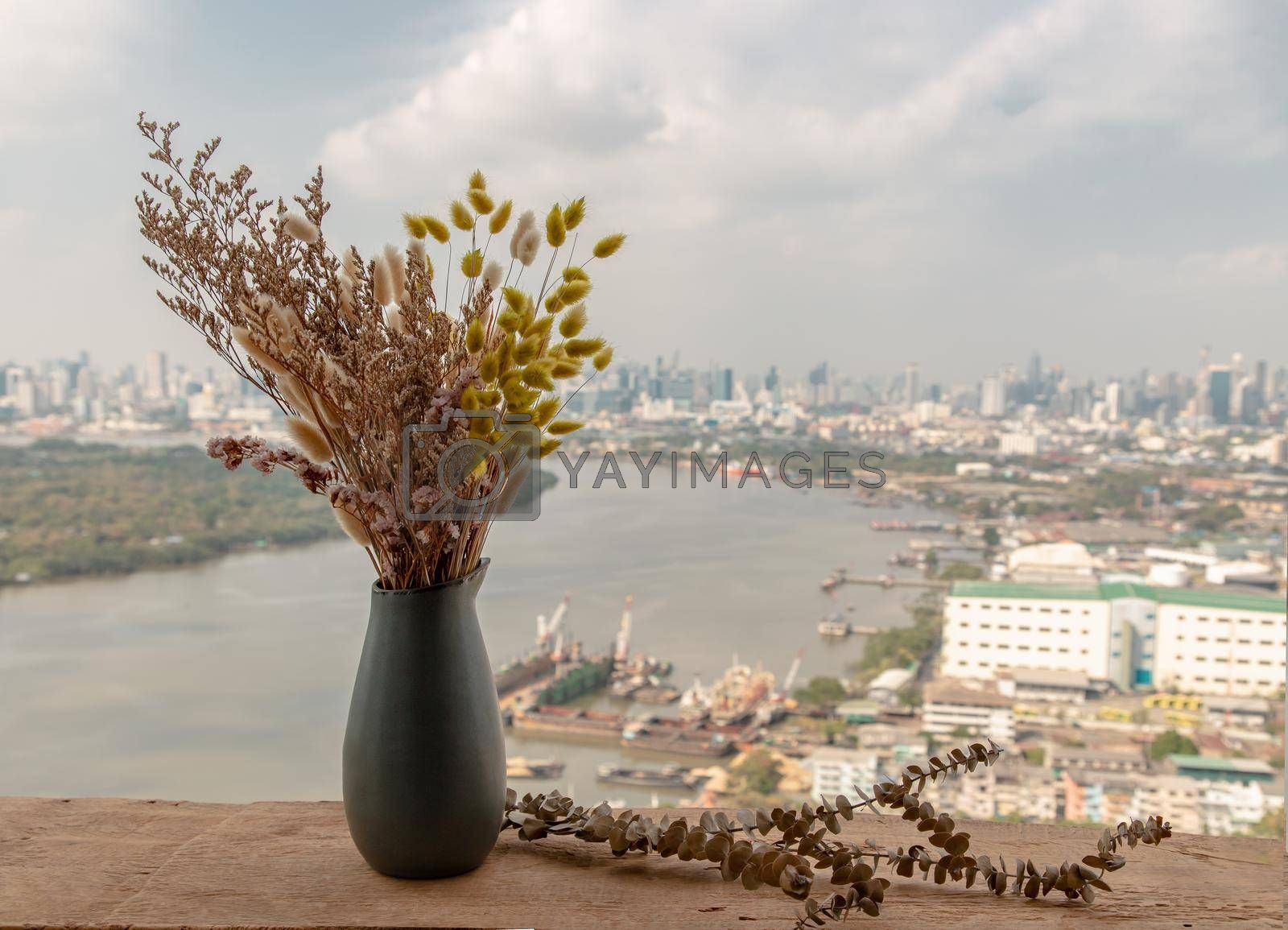 Dried flowers in ceramic vases handmade on a wooden desk on the balcony with river view background. Home decor. Space for text. Selective focus.