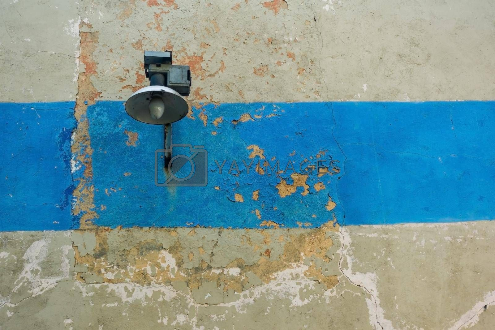 Street lamp on the wall with a crack and a blue stripe. An old wall with a street lamp. Textured wall with a lantern.