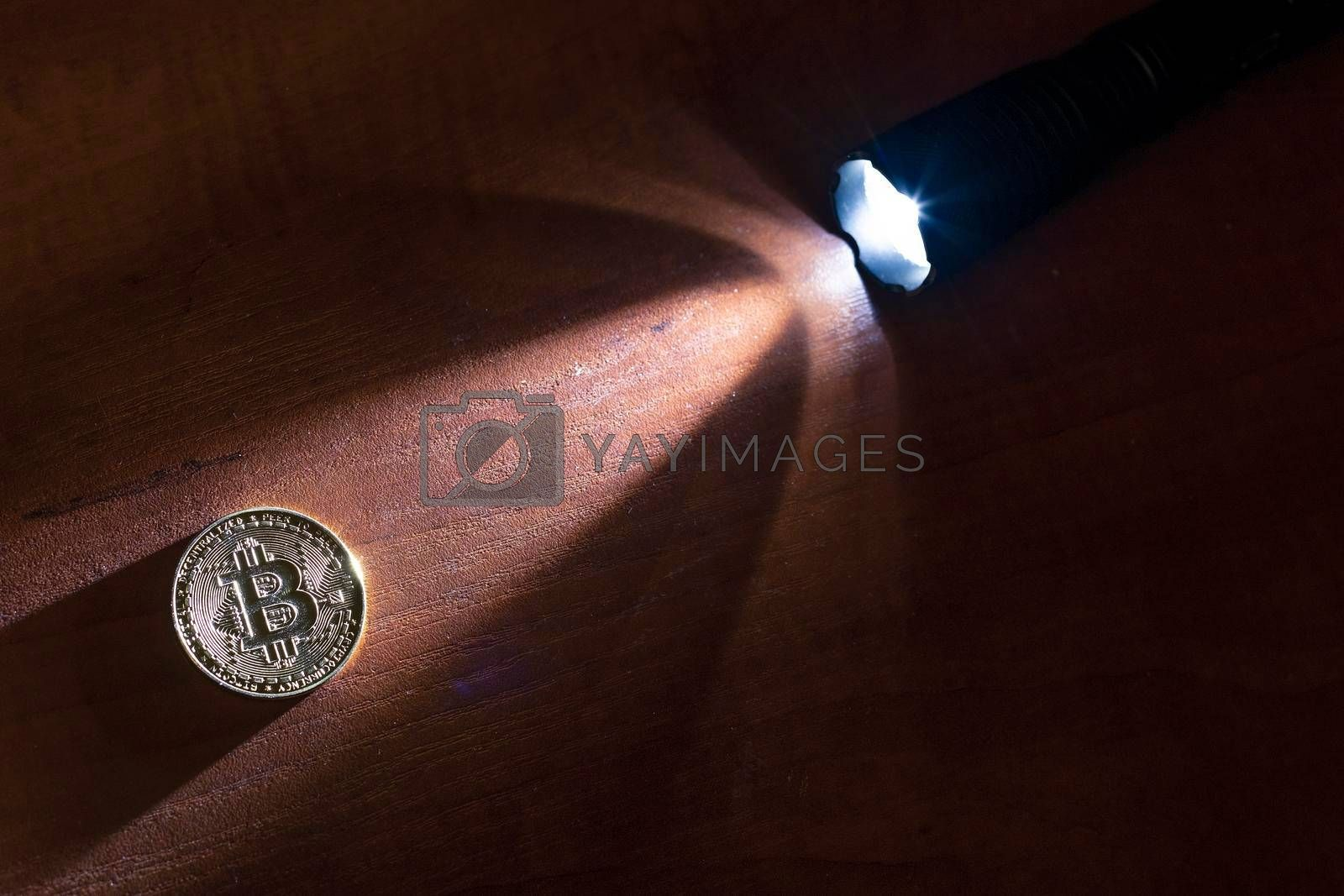 Royalty free image of Bitcoin coin lit by a ray of light from a flashlight. by Jannetta