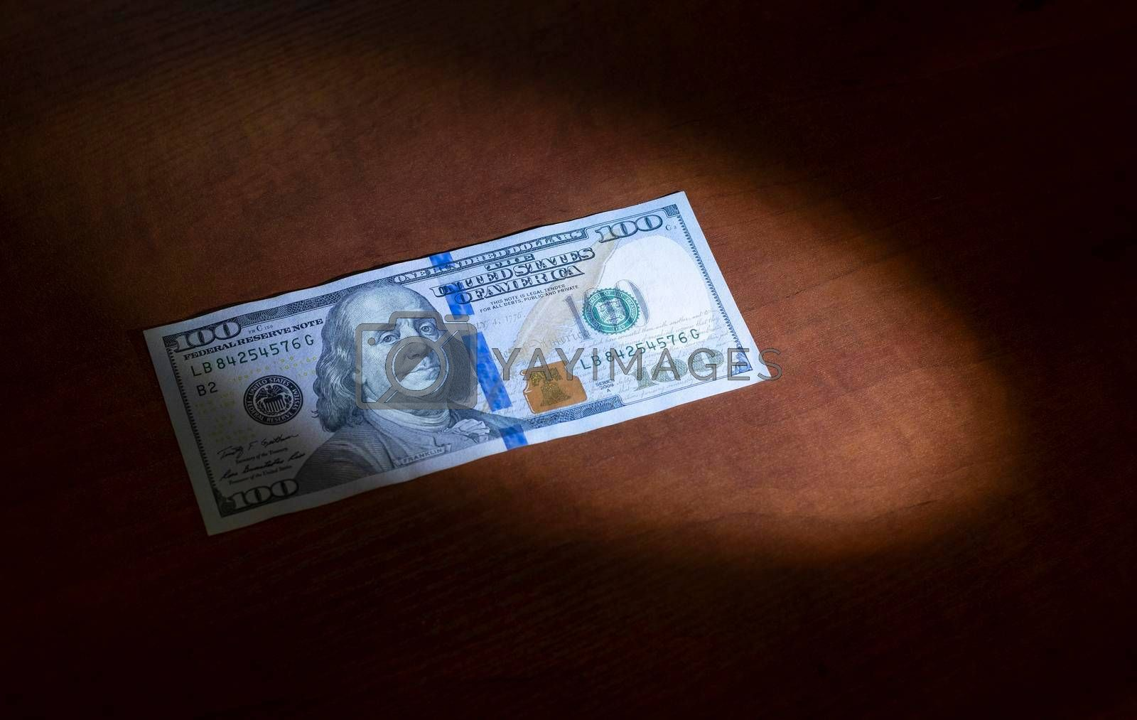Royalty free image of One hundred dollars was lying on the table and half lit by a ray of light. by Jannetta