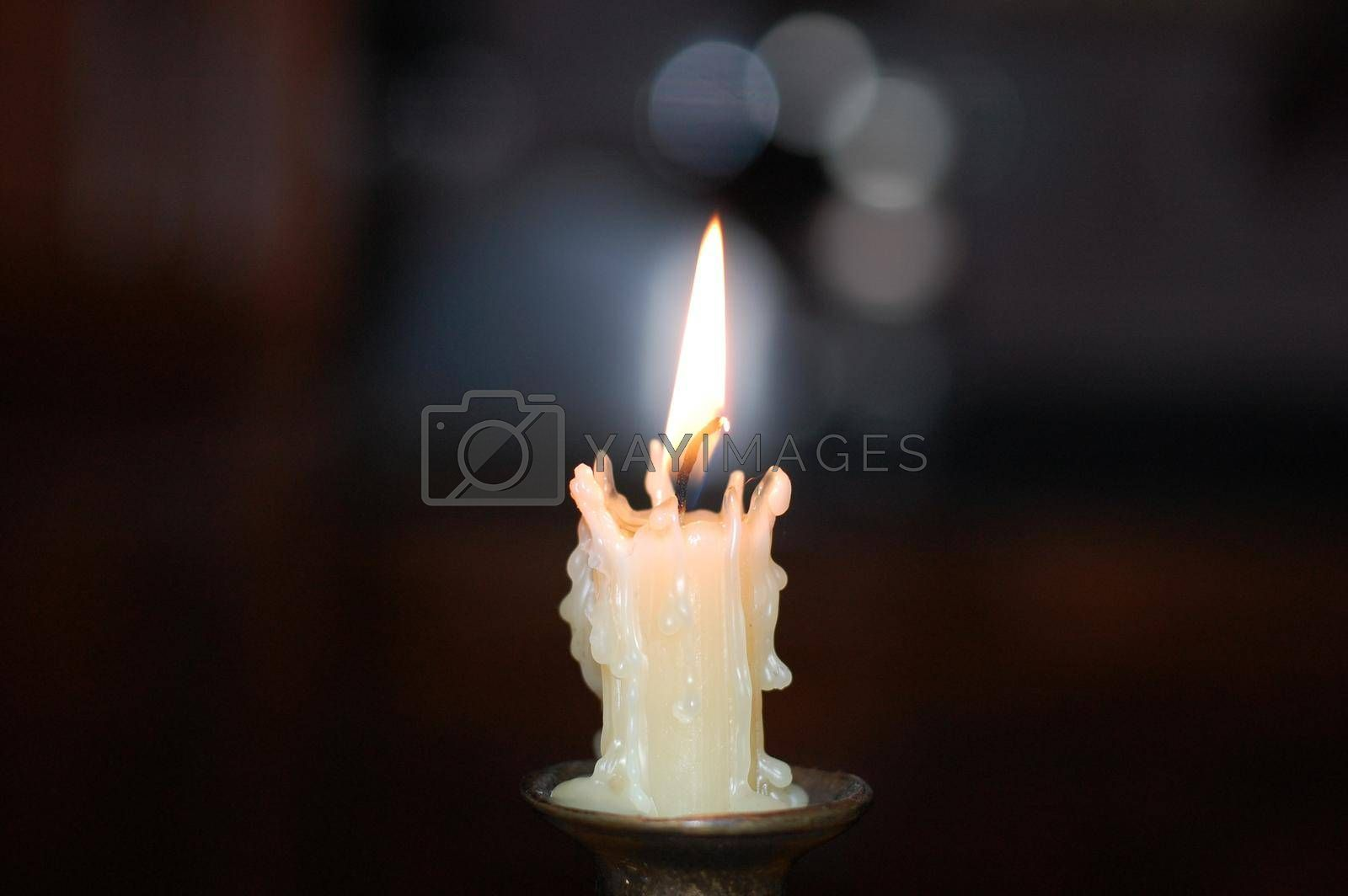 Royalty free image of White candle on a candlestick in the center. by Jannetta