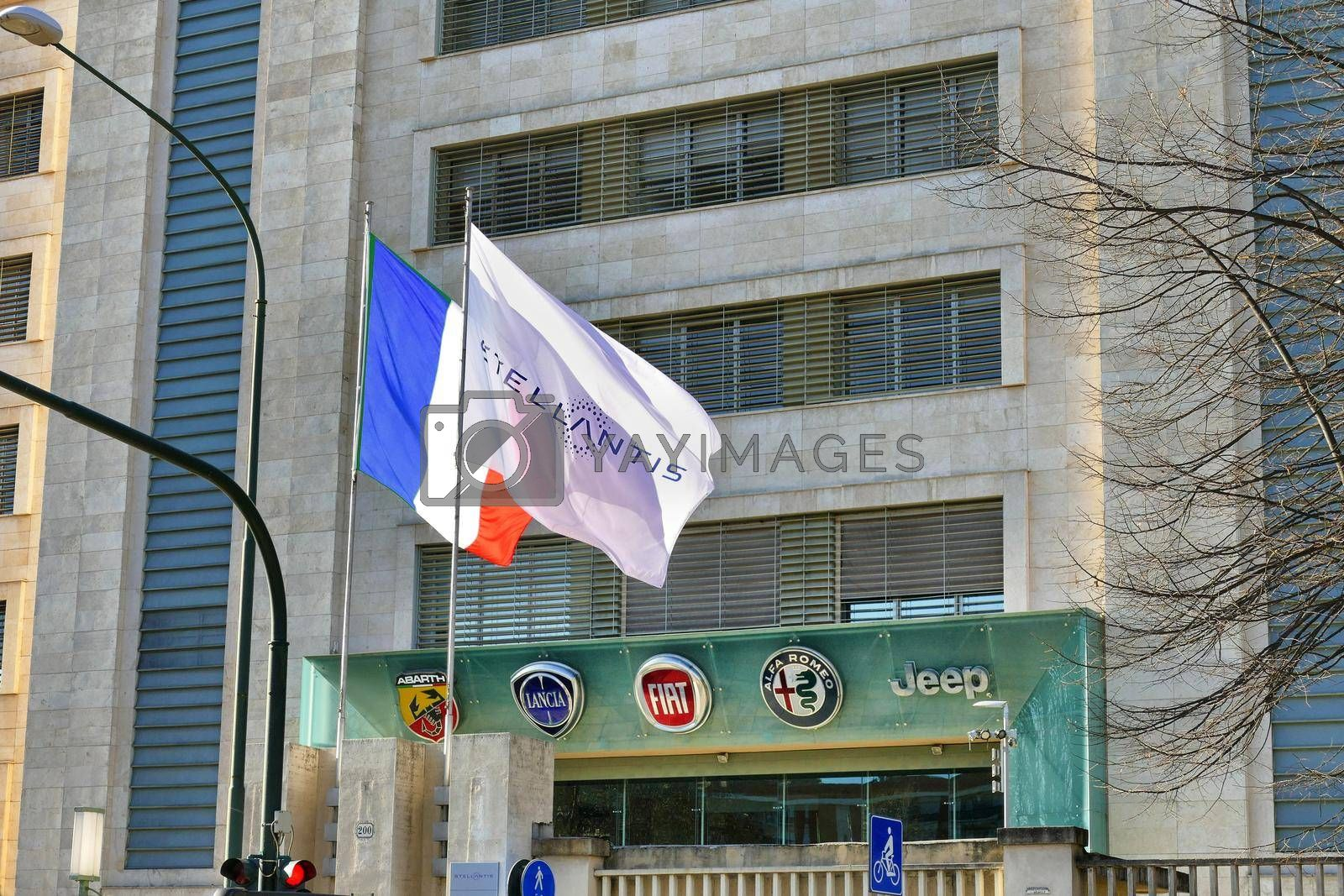 Fake French flag and Stellantis corporation flag at italian headquarters after merging between Groupe PSA and FCA automotive representing the actual control Turin Italy January 25 2021