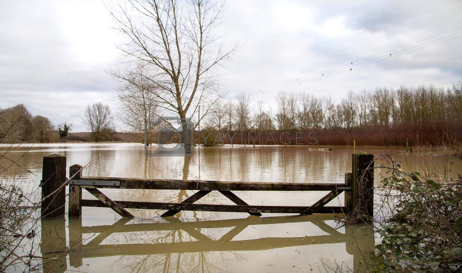 Flooded agricultural farm fields with wooden gate, sky, reflection in water, soaked field. High water in spring, UK, Suffolk spring 2021