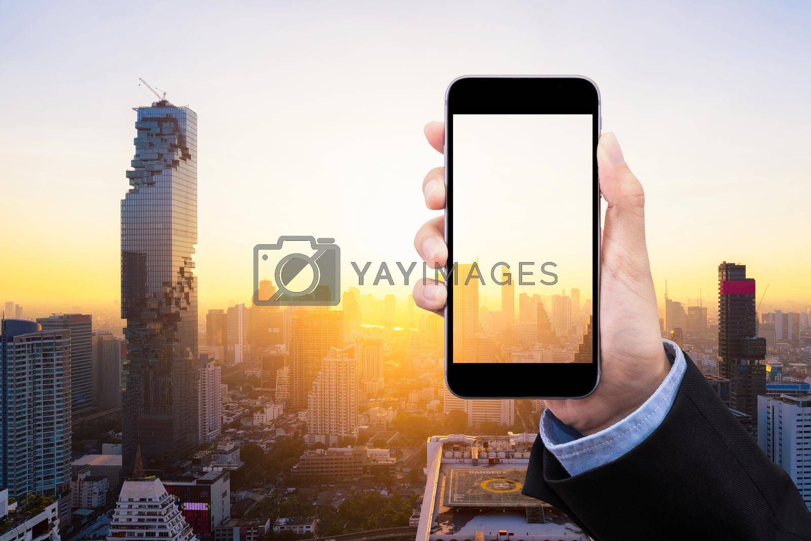 Business woman showing smartphone with transparent screen and copy space on smart city in background. Elegant design for business and smart city concept.