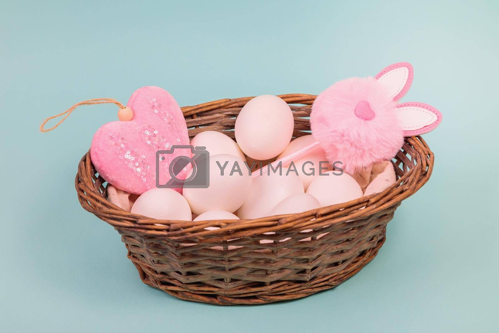 Easter. White eggs in a basket with an artificial rabbit, on a uniform blue background. Place for text.