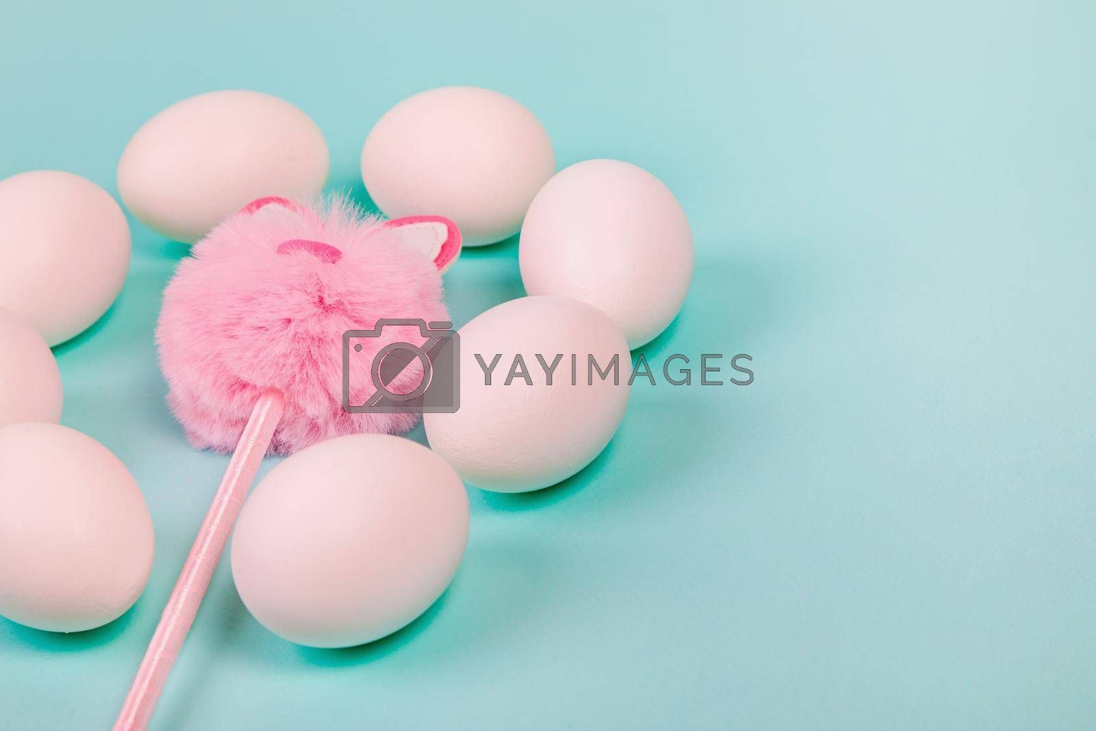 Easter. White eggs with an artificial rabbit on a uniform blue background. Place for text.
