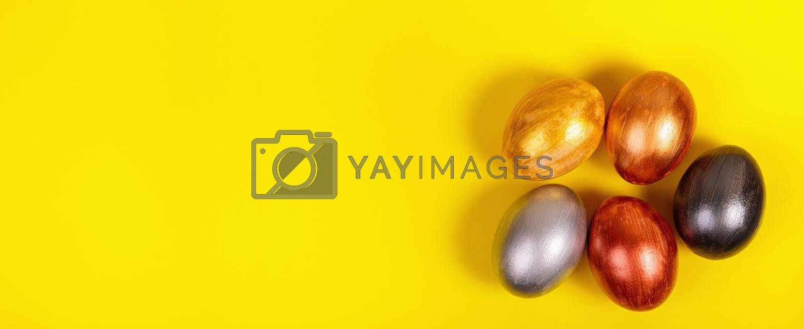 Easter. Multi-colored eggs on a uniform yellow background with place for text. View from above. Banner