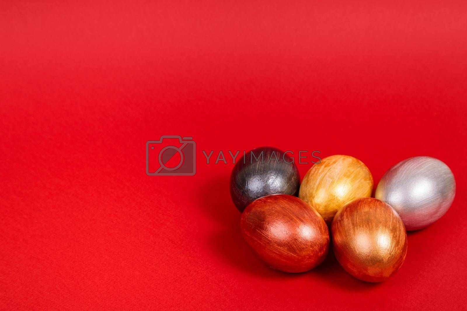 Easter. Multi-colored eggs on a uniform red background with place for text. View from above.