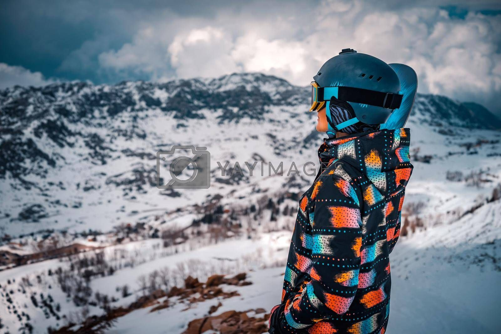 Snowboarder Girl Looks into the Distance at a Beautiful Winter Mountain Landscape. Active People Enjoying Ski Resort. Happy Wintertime Vacation.