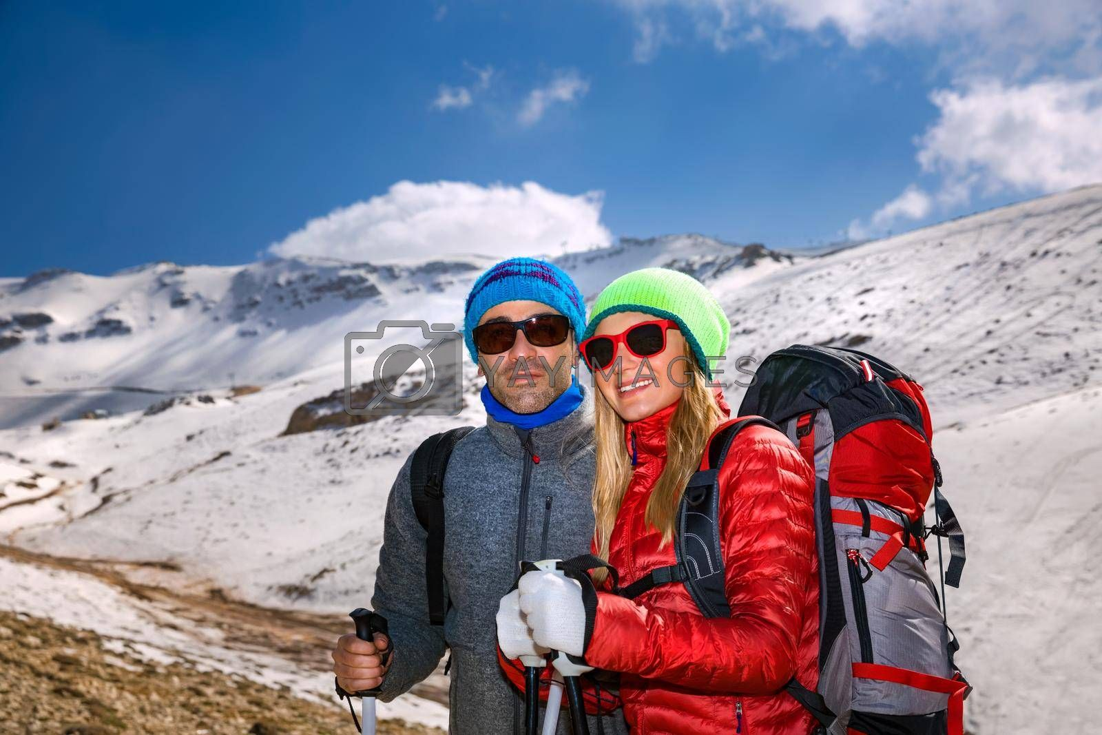 Portrait of a Nice Couple Climbing the Mountain with Trekking Poles. Enjoying Amazing View. Happy Active Winter Holidays.