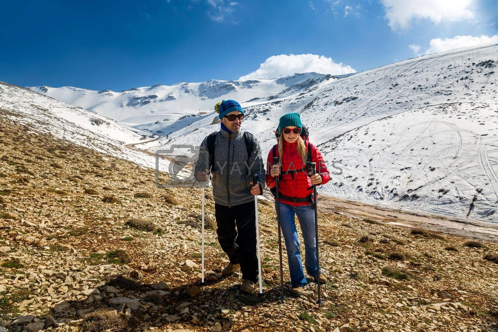 Nice Couple Climbing the Mountain with Trekking Poles. Enjoying Amazing View. Happy Active Winter Holidays. Wintertime Sport. Zest for Life.