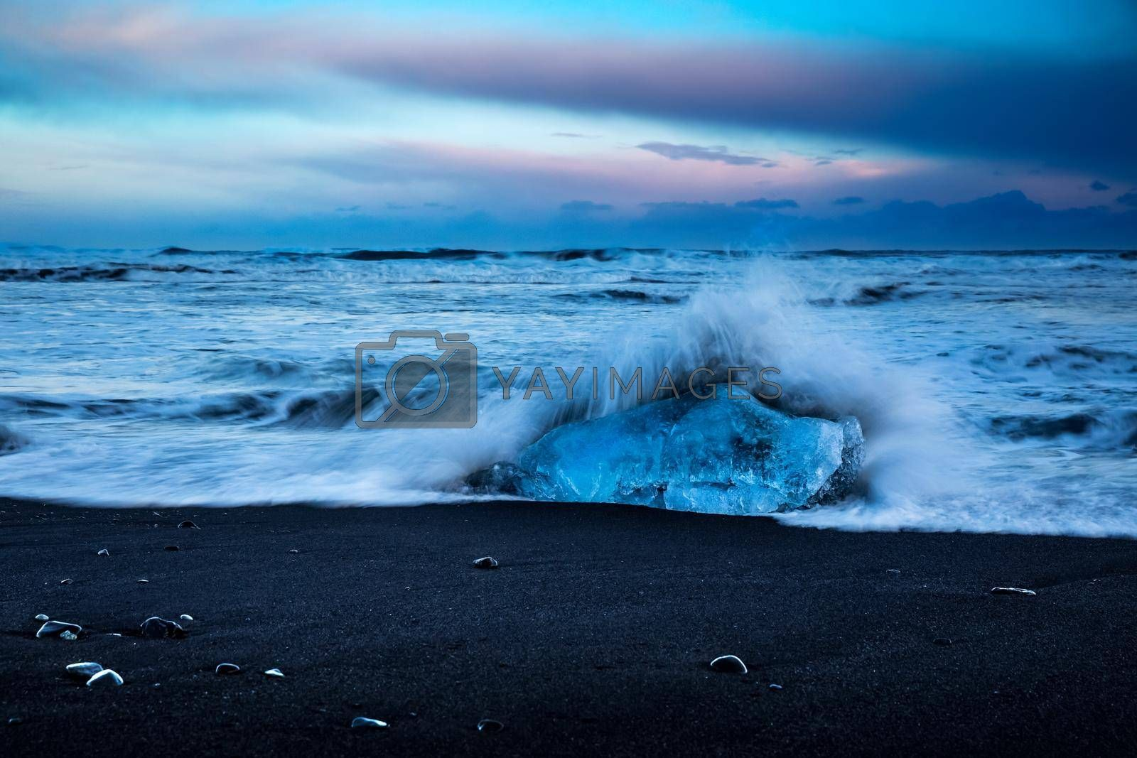 Beautiful Landscape of a Black Volcanic Sand Beach with Icebergs. Waves Against a Large Block of Ice on the Shore. Amazing Nature of Vatnajokull Jokulsarlon. Iceland.