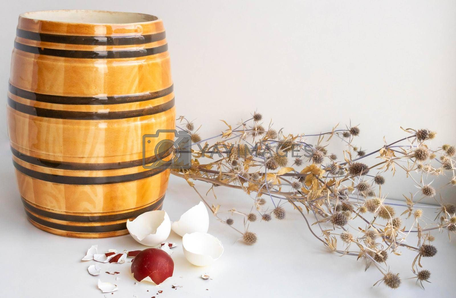 Easter. Still life with eggshells, clay barrel and dried flowers on a white background.