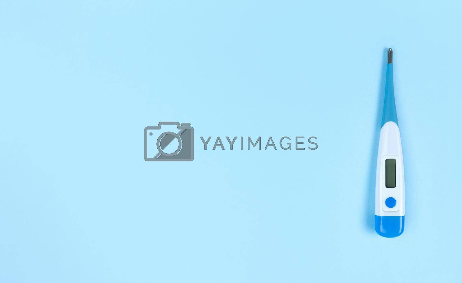 Electronic thermometer on a blue background with copy space.