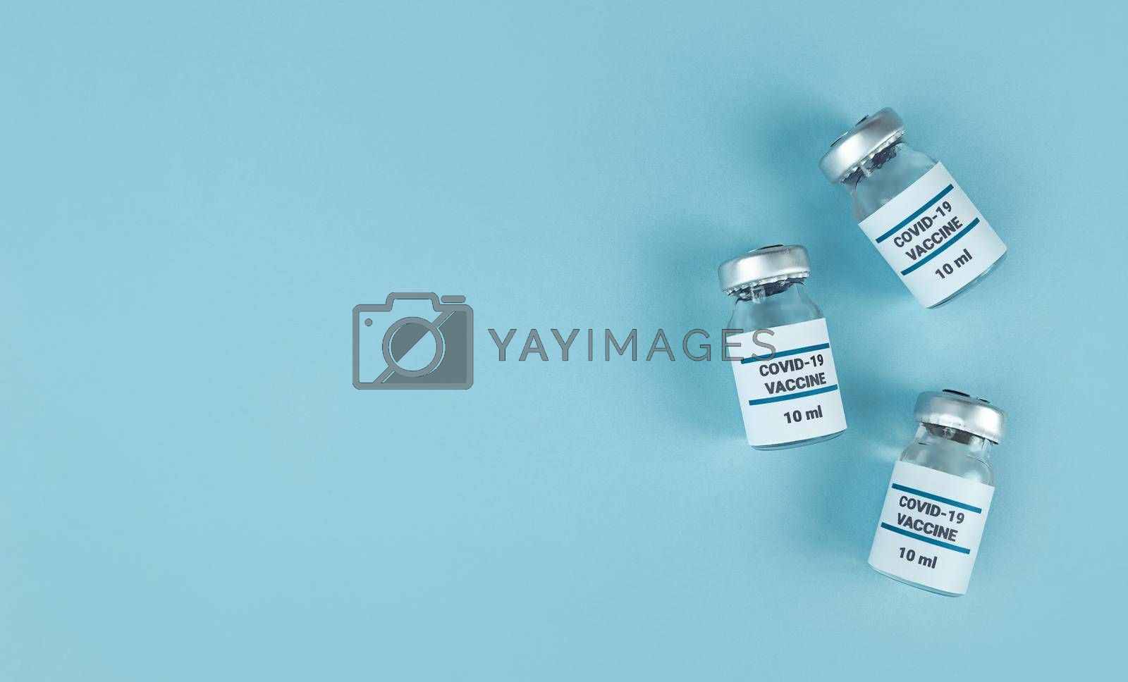 Medicine bottles with covid 19 vaccine on blue background with copy space.