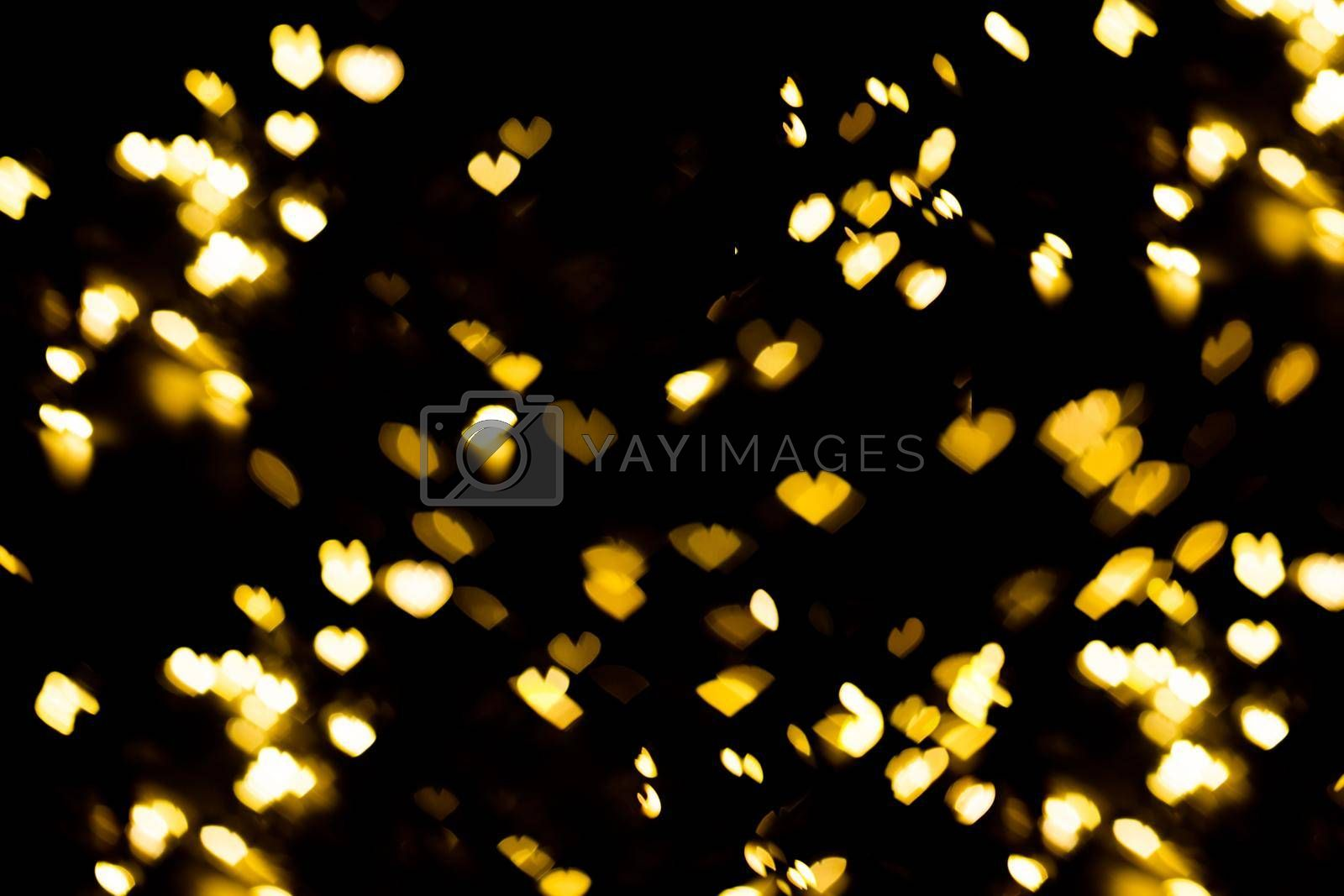 Golden shining bokeh on black background. Decoration for valentine's day or christmas background.Blurred and soft focus.