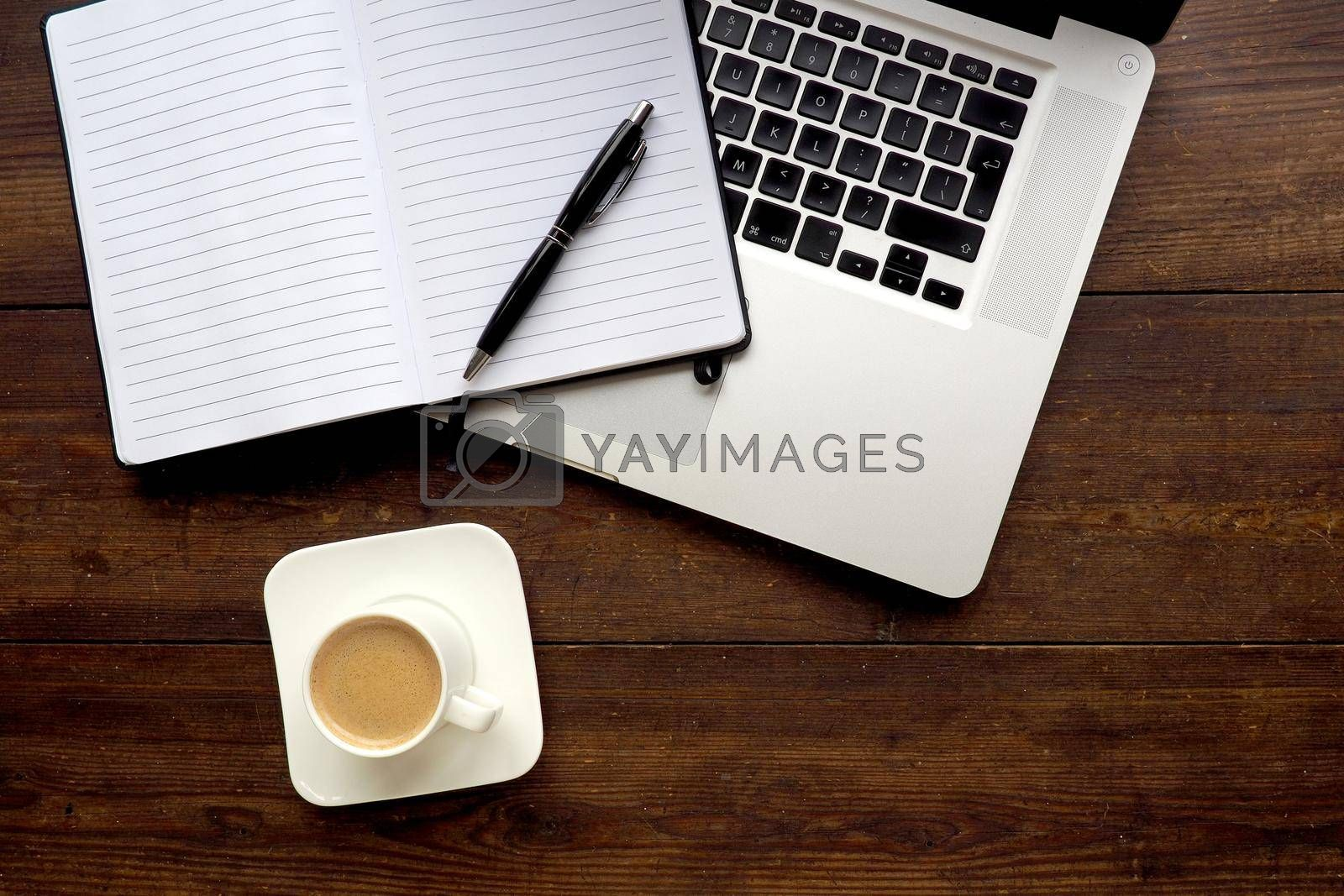 Coffee and notepad with computer, wooden desk