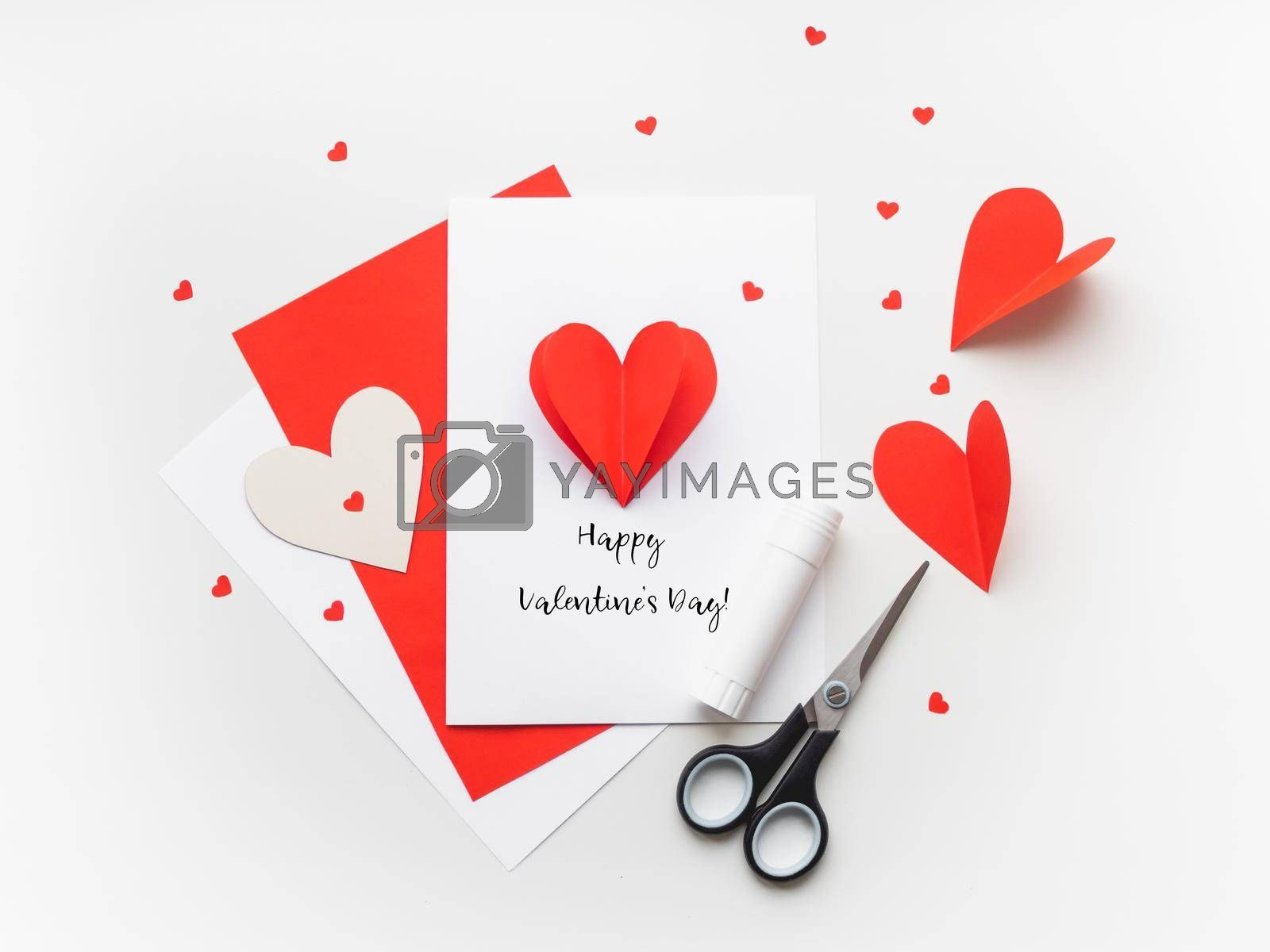 Valentine's Day greeting card. DIY holiday card with red paper volumetric heart, symbol of love and romance. Handmade card made with scissors, glue and colored paper. by aksenovko