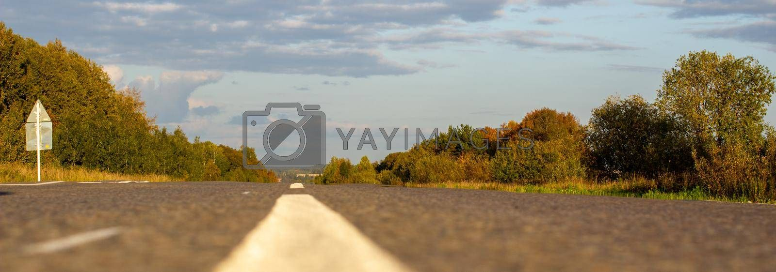 A long white stripe, like a road marker. A road into the distance between fields and forests. High quality photo